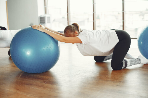 Using an exercise ball for Spine decompression exercises. Sydney Sports and Exercise Physiology